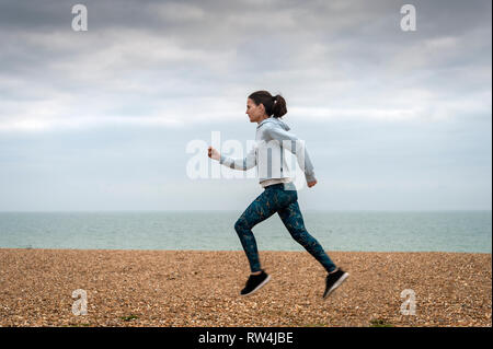 woman running along a pebble beach by the sea, keep fit. - Stock Image