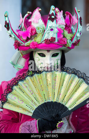 Venice, Italy. 25th Feb, 2014. Head and shoulders portrait of a masked and costumed attendee of the Carnivale holding a fan in front of her face. Venice Carnivale - Tuesday 25th February. Credit:  MeonStock/Alamy Live News - Stock Image