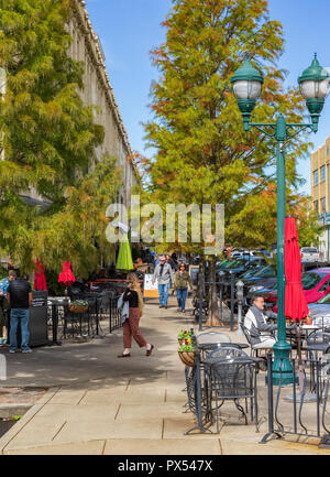 Busy scene on Page Ave. includes woman on phone, couple walking, man at table. - Stock Image