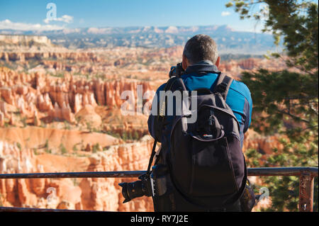 Man taking a picture from the edge of Bryce Canyon, Utah, USA. - Stock Image
