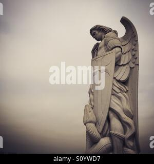 Angel statue with shield and serpent - Stock Image