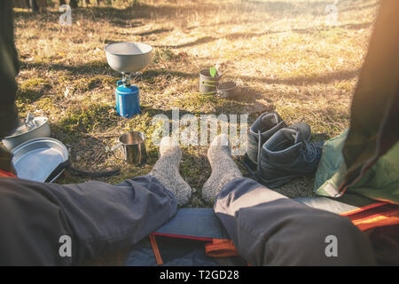 outdoor tourism - hiker feet with wool socks out of the tent - Stock Image
