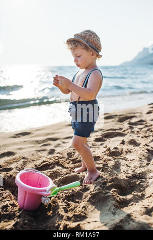 A small toddler boy standing on beach on summer holiday, playing. - Stock Image
