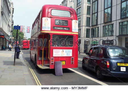 A London taxi negotiates its way around a broken down Routemaster bus, in the Strand, central London, UK. - Stock Image