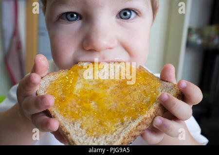 Little baby boy eating peach jam toast. Closeup - Stock Image
