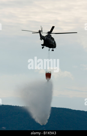 Slovenian Cougar helicopter dropping water during fire fighting demonstration, Airshow Maribor 2008, Slovenia June - Stock Image