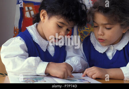 two primary school girls reading out loud - Stock Image