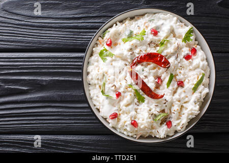 Comforting Curd Rice is a popular dish from South India with yogurt and then tempered with spices closeup in a plate on the table. horizontal top view - Stock Image