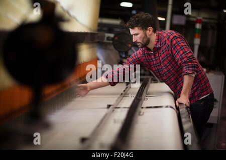 Young male weaver using old weaving machine in textile mill - Stock Image