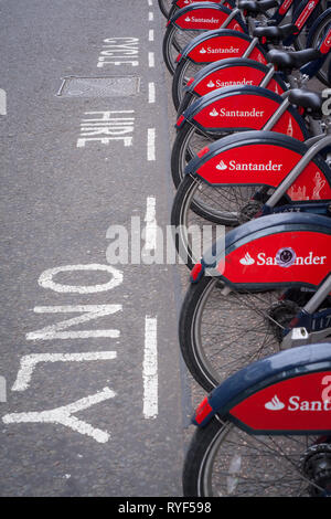 A line of Santander hire bikes in Soho, London. - Stock Image