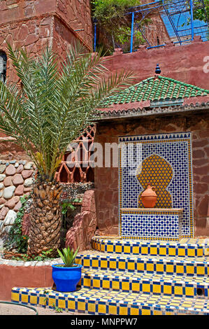 The decorated ceramic enterance to a studio pottery near Marrakech in Morocco with a palm tree - Stock Image