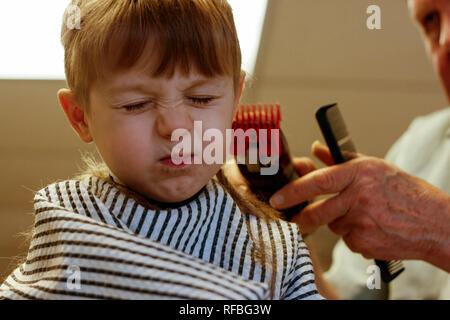 A young boy has his hair cut at a barber shop in a small town. - Stock Image