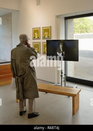 An elderly gentleman watching a video presentation in at 'Inside Out' an exhibition by Scottish artist Ronald Forbes in the STUDIO PAVILION, Glasgow - Stock Image