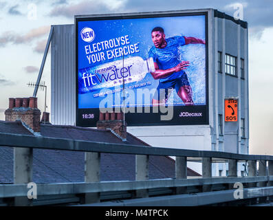 Lucozade digital billboard sportsman advert on the side of a historic 1954 concrete building, next to the M4 motorway, - Stock Image