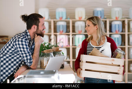 Young shop assistant serving an attractive woman in a zero waste shop. - Stock Image