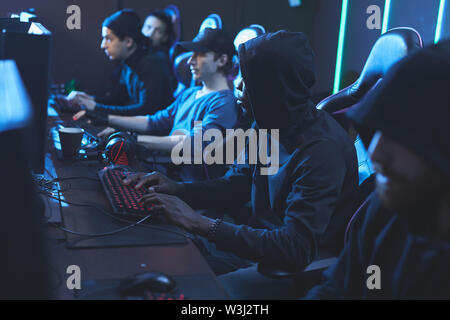 Group of concentrated young software developers in dark outfits sitting in row and working in server center - Stock Image