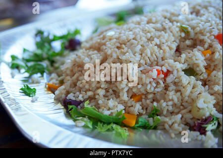 Healthy steamed brown, integral rice with vegetables on a large plate, served on its own or as a side dish, a delicious option for vegetarians - Stock Image