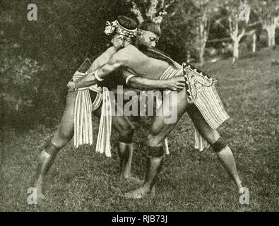 Two Kayan wrestlers of Borneo, SE Asia (then part of the British Empire) - a popular sport with the older boys and men of the tribe. - Stock Image