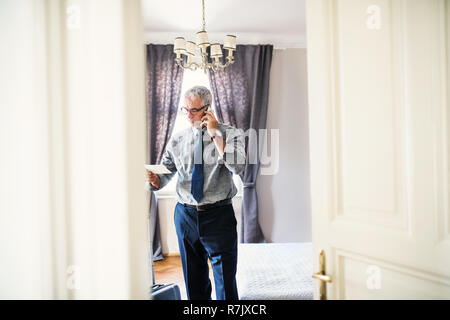Mature businessman with glasses on a business trip standing in a hotel room, making phone call. - Stock Image