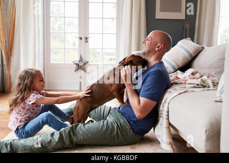 Father and daughter having fun with their pet dog at home - Stock Image