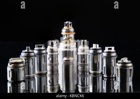 Vaporizers steel coils in a row on a reflective glass - Stock Image