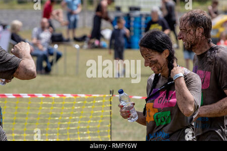 Couple covered in mud at the end of a mud run. - Stock Image