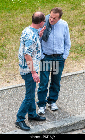Two men chatting at roadside - France. - Stock Image