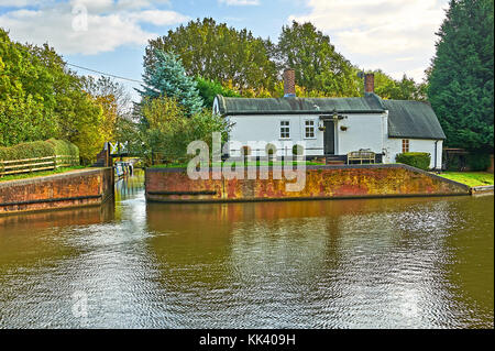 Kingswood Junction, Lapworth on the Stratford upon Avon Canal with a white walled barrel roof lock keeper cottage, - Stock Image