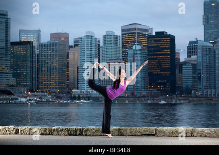 A young woman does the Natarajasana Lord of the Dance yoga pose with the city skyline beyond, Vancouver, BC, Canada - Stock Image