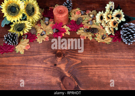 Thanksgiving decor with candle, frosted pine cones, sunflowers, acorns and maple leaves - Stock Image