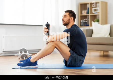 man drinking water during training at home - Stock Image