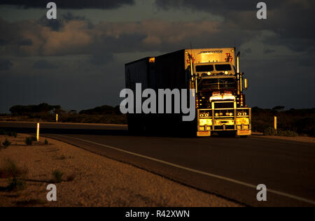 Road train travelling into sunset, Australia - Stock Image