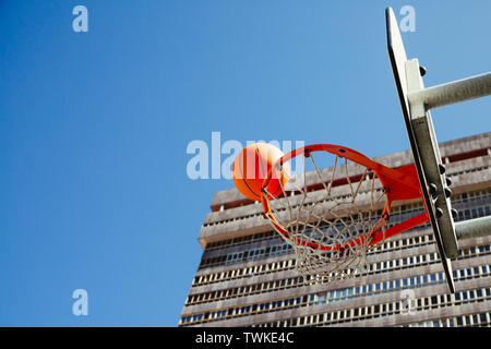Basketball hoop with ball about to score against a blue sky and a skyscraper - Stock Image