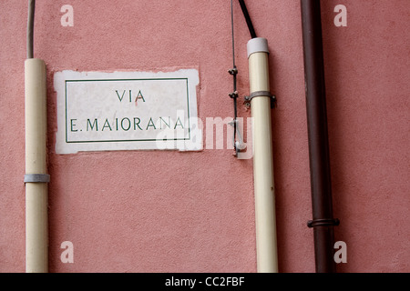 Italian street sign on a red wall which reads 'Via E. Maiorana'. Taken in Sicily Italy. - Stock Image