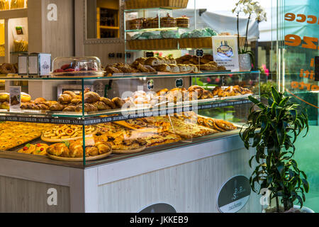 Fresh baked croissants, pizza pieces, sweet buns and other behind glass in a bar in Jesolo, Italy. - Stock Image