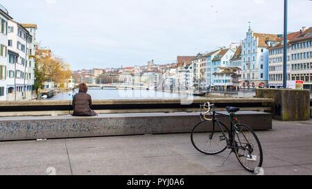 Zurich, Switzerland - March 2017: Woman with bicycle enjoying the view of river Limmat and Zurich riverside on Town Hall Bridge Rathausbrücke, Zurich  - Stock Image