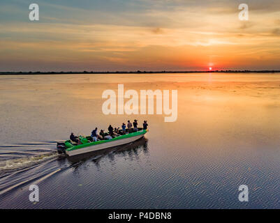 Tourists visiting Danube Delta in a motor boat, taking pictures at sunset in the Danube Delta, Romania - Stock Image