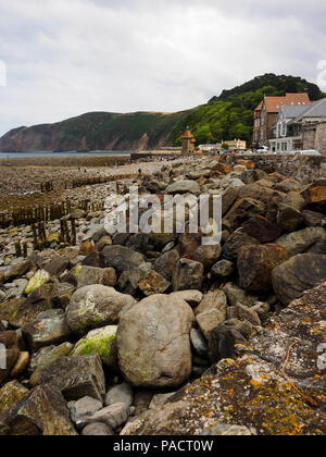 Boulder strewn foreshore exposed at low tide at Lynmouth, Devon, Uk.  Foreland point in the dustance. - Stock Image