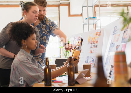 Creative designers people designing bottle label in office - Stock Image