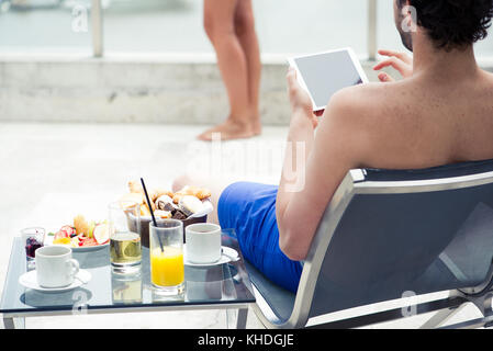 Man relaxing by pool using digital tablet - Stock Image