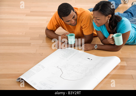 African American male and female couple lying on floor looking at architectural blueprints - Stock Image