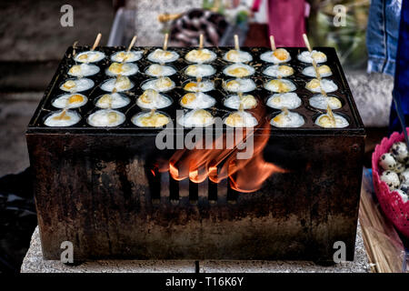 Thailand street food with quail eggs cooking on a flame stove at a Thai market stall. - Stock Image