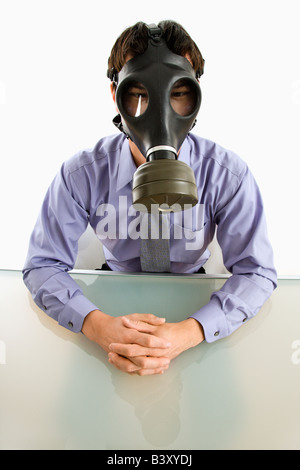 Businessman sitting in white room wearing gas mask - Stock Image