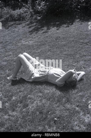 1950s, summertime and a young lady wearing a light cotton dress lying on the ground with her arm across part of her face... as if to say you can photo me but not know me! - Stock Image