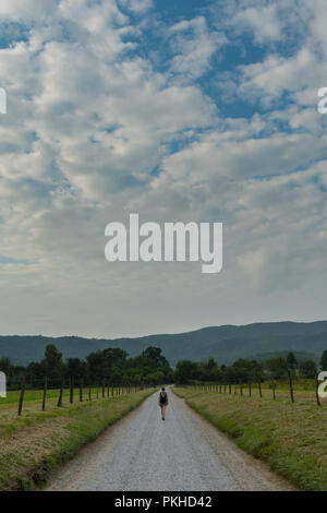 Hyatt Lane and Woman Walking Under Cloudy Sky in Late Summer - Stock Image