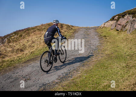 Male cyclist, cycling from Poolewe to Cove along the shore of Loch Ewe, west coast of Scotland. - Stock Image