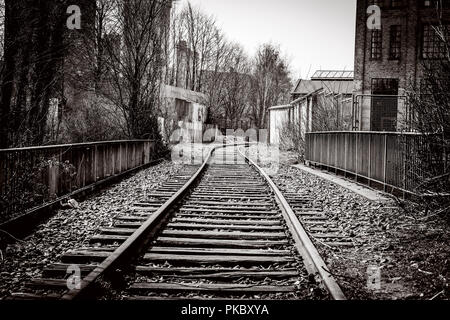 Railroad tracks going through an abandoned city with old buildings - Stock Image