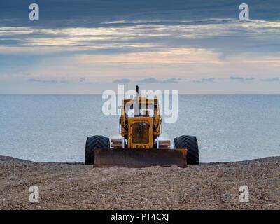 Bulldozer used as mobile fishing boat launcher and beach shingle scraper on Aldeburgh beach Suffolk England - Stock Image