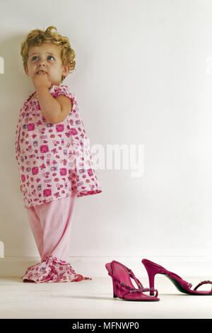 Child 18 months standing in corner, with pair of high heel shoes in foreground. Model released. Studio shot      Ref: CRB538_103609_0001  COMPULSORY C - Stock Image
