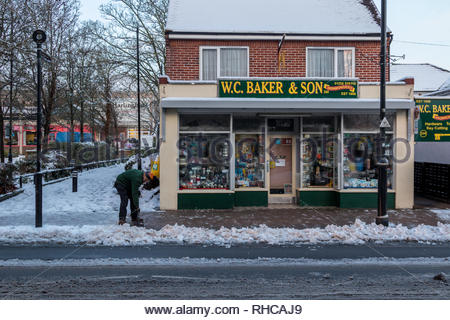 Fleet, Hampshire, UK. 2nd Feb, 2019. Heavy overnight snow followed by a sharp frost made for a difficult early morning for pedestrians and motorists. Image: A staff member clears snow from the pavement in front of Bakers. An old-fashioned ironmongers, the shop has been trading in Fleet for over 100 years. Credit: Images by Russell/Alamy Live News - Stock Image